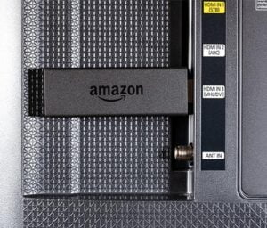 a firestick tv device inserted into the HDMI port of the back of a tv