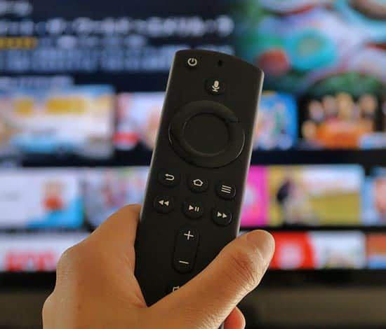 a man holding up the remote controll of a firestick tv