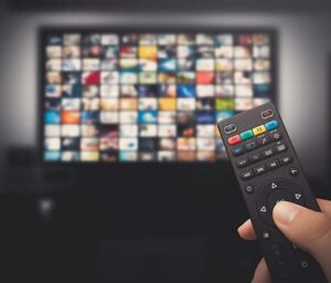 a person pointing a remote towards a tv in order to stream content