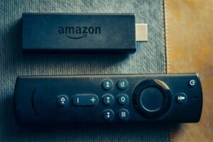 An image featuring an Amazon FireStick and a TV remote