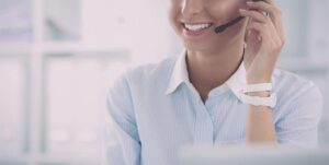 An image featuring a person smiling and working on the computer representing a customer service