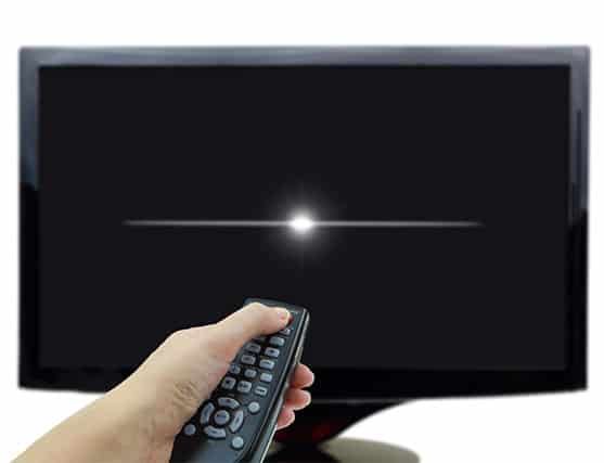 An image featuring a person using his TV remote to shut down his TV