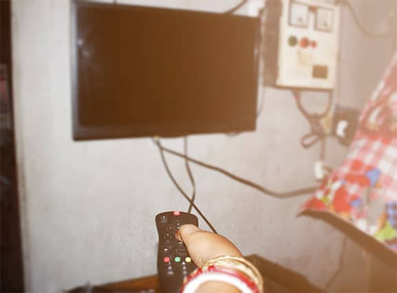 An image featuring a person holding out his TV remote trying to power on his TV