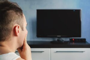 An image featuring a person looking confused as to why his TV screen is off representing TV issues