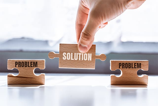 An image featuring a person holding a puzzle in his hand that says solution