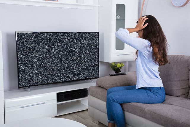 An image featuring a woman getting frustrated with her TV flickering issue