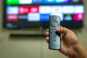 An image featuring a person holding an Amazon FireStick remote and using his TV
