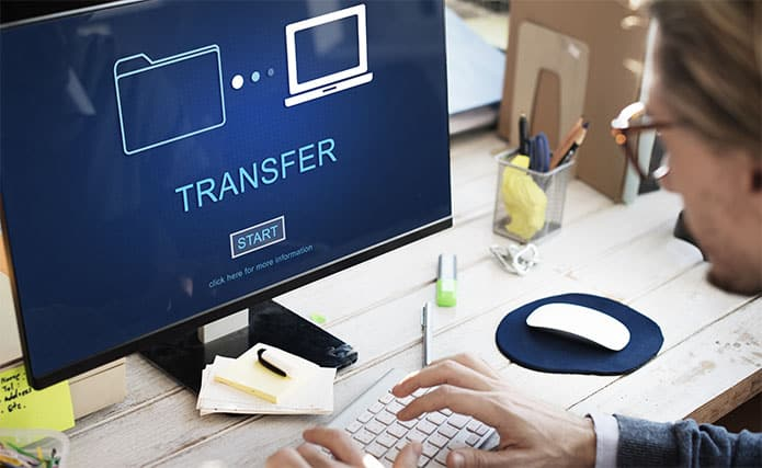 An image featuring a person using his PC to transfer files