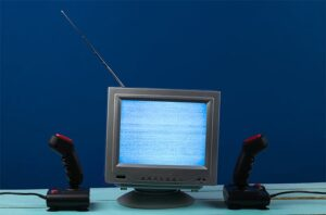 An image featuring game emulators concept with an old TV in the middle with two controllers next to it
