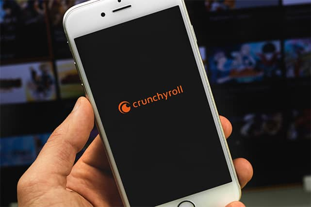 An image featuring a person holding his phone while opening Crunchyroll