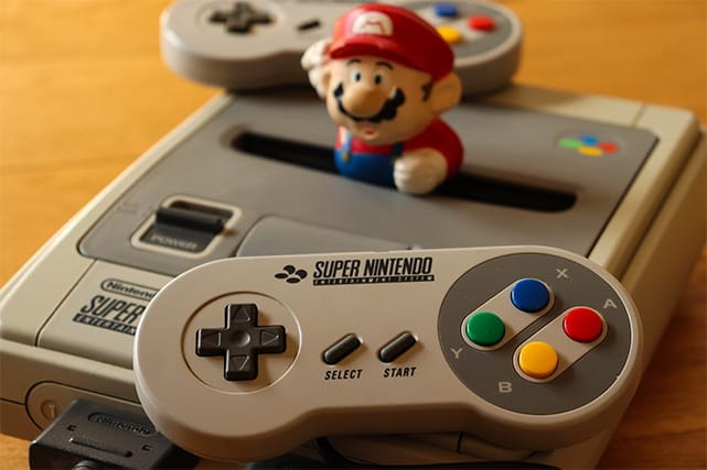 An image featuring the Super Nintendo Entertainment System with Super Mario on top of it