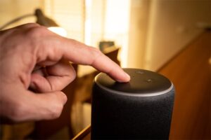 An image featuring a person pointing out his finger and pressing an Alexa device