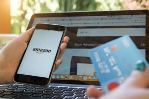 An image featuring a person holding her credit card in one hand and has opened Amazon on her phone in her other hand with a laptop in the background representing Amazon shopping concept