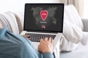 An image featuring a person laying and using his laptop while being connected to a VPN