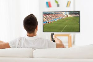 An image featuring a person holding his TV remote and watching TV in the background