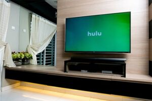 An image featuring a big TV in a living room with Hulu opened on it
