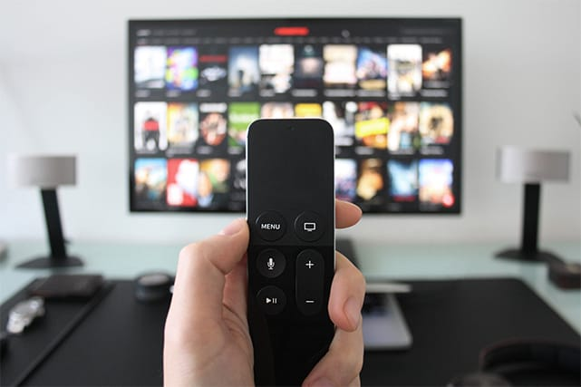 An image featuring a person holding a TV remote while watching online streaming TV channels in the background
