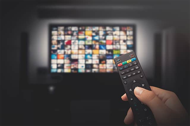 An image featuring a person holding his TV remote and watching TV representing Fire Anime FireStick concept