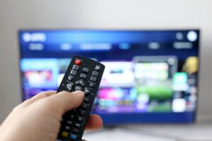 An image featuring a TV with a person holding their remote control in front