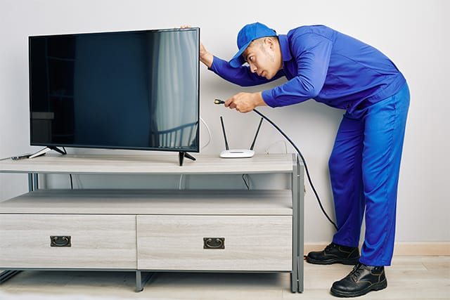 An image featuring a person connecting a cable on the TV representing cable for FireStick concept